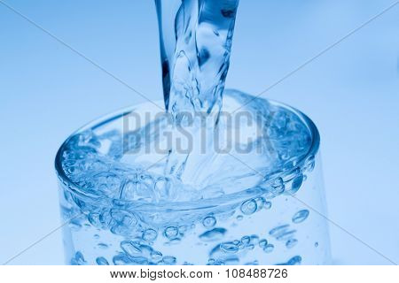 pour water into a glass, symbol photo for drinking water, abundance and waste