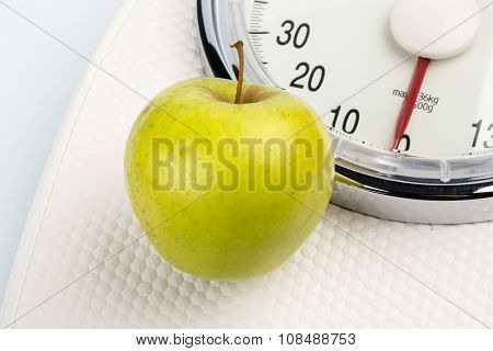 on a personal scale is an apple. photo icon for weight loss and healthy, vitamin-rich diet.