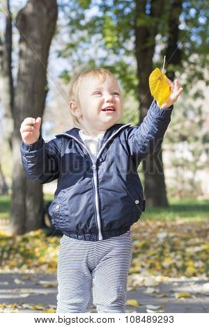 Cute One Year Old Baby Girl Playing With A Leaf In A Park