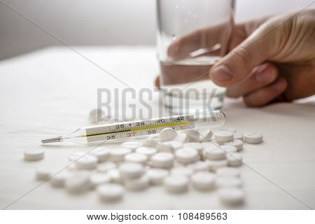 Medical Thermometer And On The Table White Pills And Hand Reaches For A Glass Of Water