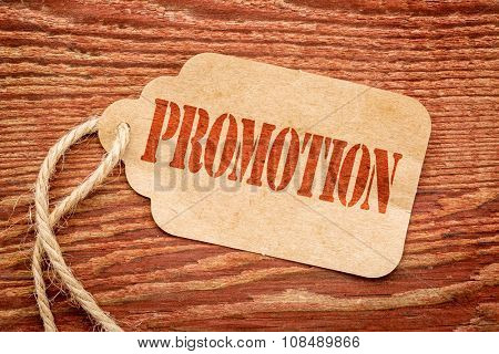 promotion - red stencil text on a paper price tag against grunge wood, marketing concept