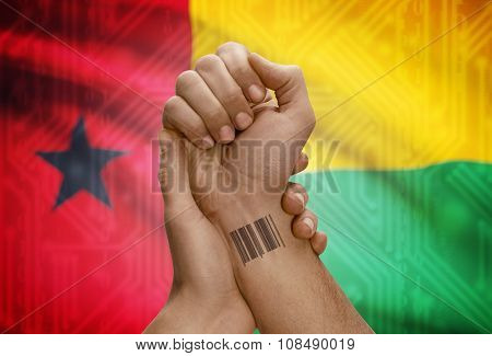 Barcode Id Number On Wrist Of Dark Skinned Person And National Flag On Background - Guinea-bissau