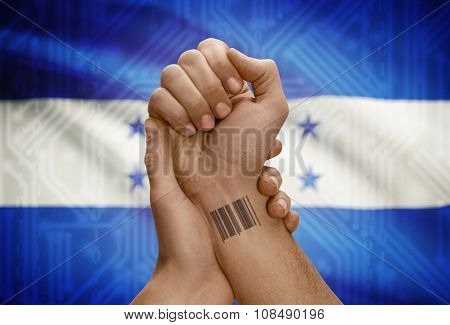 Barcode Id Number On Wrist Of Dark Skinned Person And National Flag On Background - Honduras