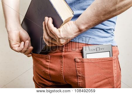 In The Back Pocket Of Jeans Is An E-book, A Man Tries To Shove In A Second Pocket Paper Book
