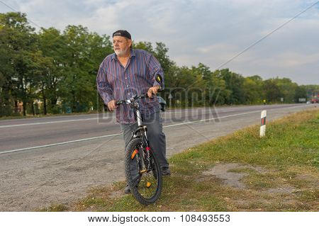 Bearded senior man on the roadside getting ready to ride on bicycle