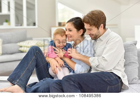 Young parents with baby sitting in sofa at home