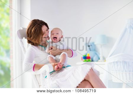 Mother And Baby In White Bedroom
