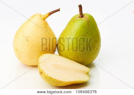 Green and yellow pear with half on white