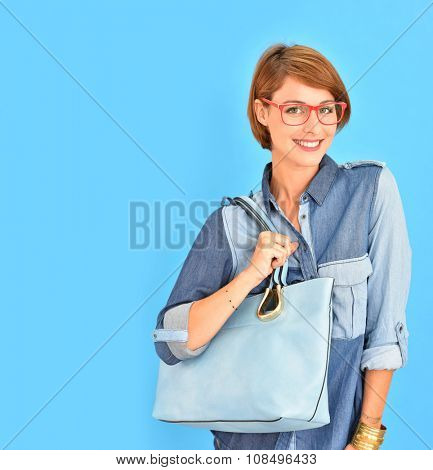 Atractive city girl with red glasses, isolated on blue background