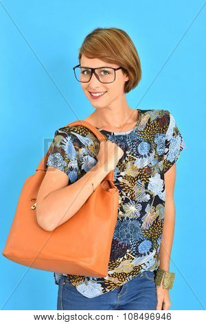 City girl with purse and eyeglasses standing on blue background