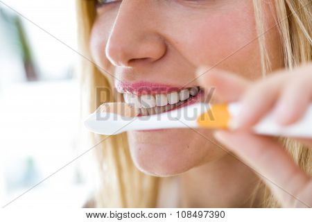 Pretty Young Blonde Woman Cleaning Her Teeth.