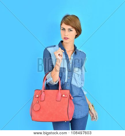 Attractive young woman on blue background holding red purse