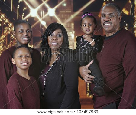 An attractive African American family outside a Christmas-lit mall.