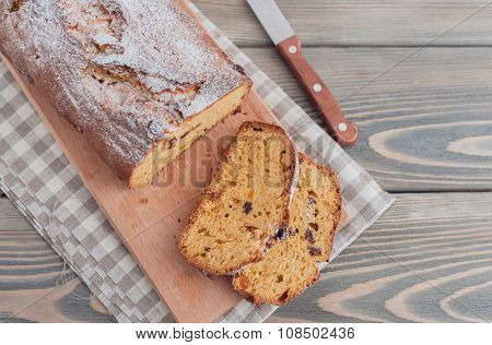 Homemade cake with dried apricots and raisins on wooden background.