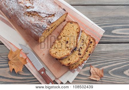 Homemade cake with dried apricots and raisins on wooden background.  Autumn still life.