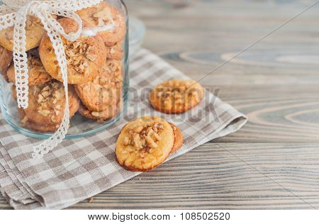 Delicious homemade cookies with walnuts on wooden background.