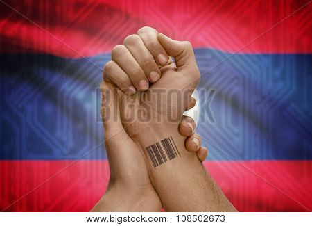 Barcode Id Number On Wrist Of Dark Skinned Person And National Flag On Background - Laos