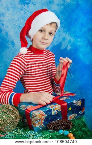 Boy In Santa Hat Tieing Red Ribbon On Blue Box