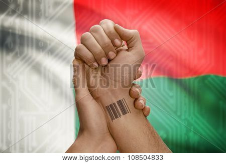 Barcode Id Number On Wrist Of Dark Skinned Person And National Flag On Background - Madagascar