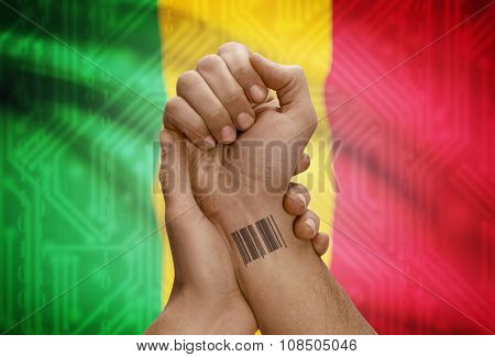 Barcode Id Number On Wrist Of Dark Skinned Person And National Flag On Background - Mali