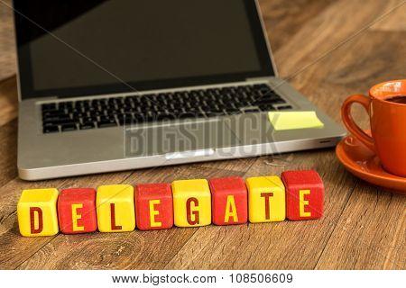 Delegate written on a wooden cube in a office desk