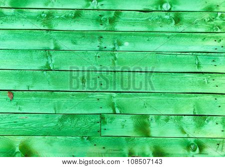 Bright green wood texture background with parallel stained colorful planks or boards in a decking or wall, full frame