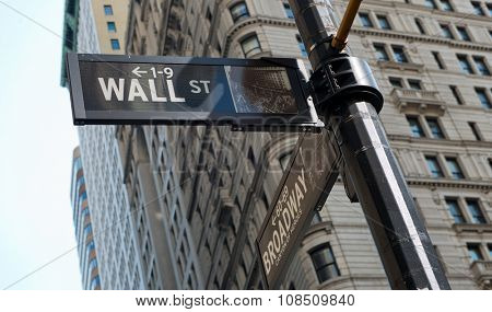 Low Angle View of Signs at Intersection of Wall Street and Broadway Street, Affixed to Post with View of Highrise Buildings in Background, New York City, New York, USA