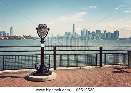 View of New York City Skyline on Sunny Day with Viewfinder Binoculars in Foreground, as seen from Liberty Island, New York, USA