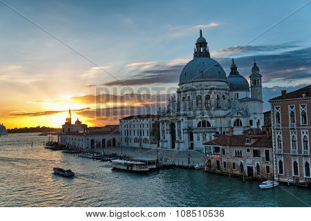 Colorful orange sunset over the Grand Canal, Venice, Italy with the Basilica Santa Maria della Salute and a water bus or vaporetto and private boats on the canal