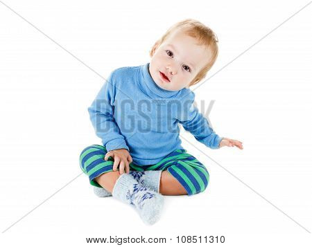 Cute Happy Baby Blonde In A Blue Sweater Playing And Smiling On White