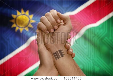 Barcode Id Number On Wrist Of Dark Skinned Person And National Flag On Background - Namibia