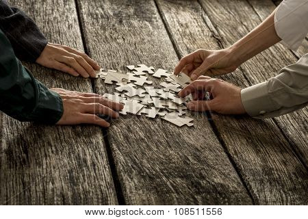 Pile Of Puzzle Pieces Lying On Wooden Desk With Four Hands Reaching To Each Take One