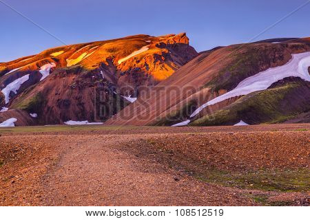 Morning dawn in national park Landmannalaugar, Iceland. Mountains and glaciers covered with warm pink and orange sunlight