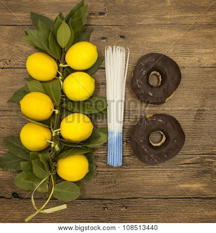 Branch lemons  donuts candles  crown of thorns. Symbols of the great holiday of Hanukkah. On wooden background