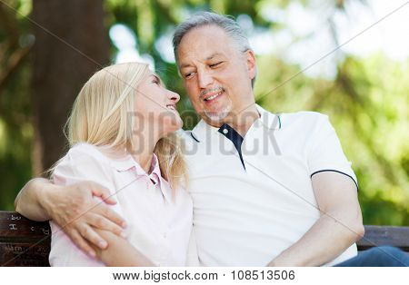 Happy mature couple sitting on a bench