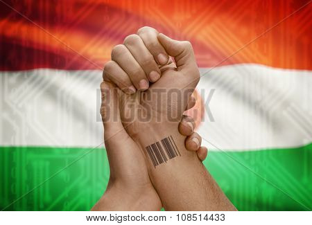 Barcode Id Number On Wrist Of Dark Skinned Person And National Flag On Background - Niger