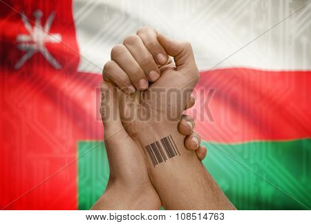 Barcode Id Number On Wrist Of Dark Skinned Person And National Flag On Background - Oman