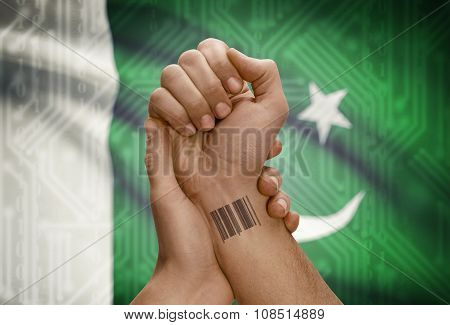 Barcode Id Number On Wrist Of Dark Skinned Person And National Flag On Background - Pakistan