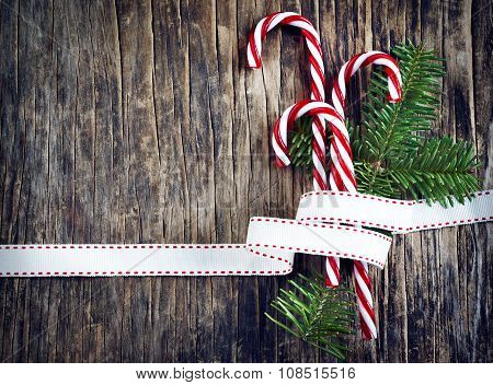 Candy Cane With White And Red Ribbon On Wooden Background