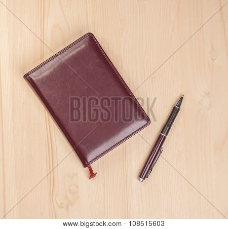 Notebook With Pen On Wooden Table