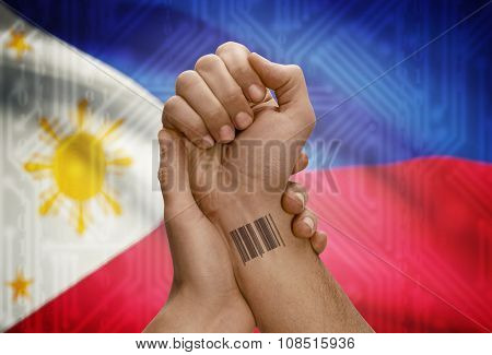 Barcode Id Number On Wrist Of Dark Skinned Person And National Flag On Background - Philippines