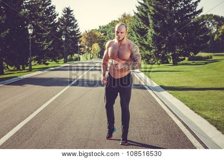 Young strong male fitness model during run outdoors in beautiful landscape.