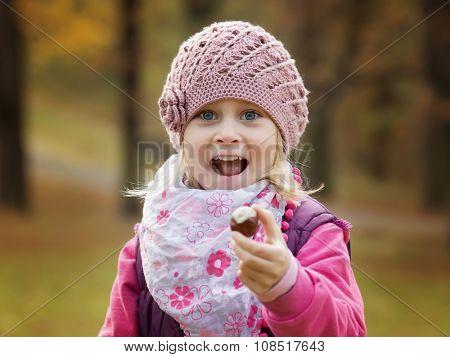 Portrait little girl in autumn parkto hold in hand chestnut