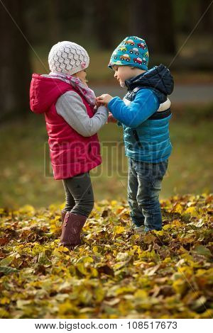 Portrait of two kids in the park as they talk together