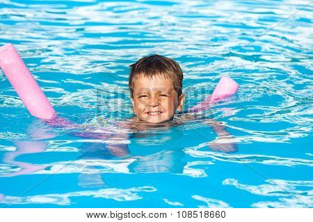 Happy small boy learns to swim with pool noodle