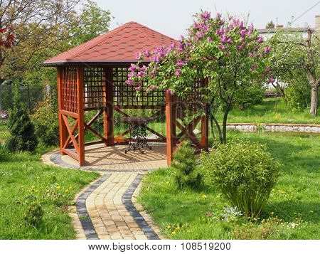 Arbor in garden with lilac horizontal