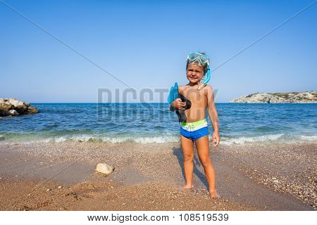 Boy with mask and paddles stands on the seashore