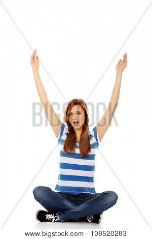 Happy teenage woman sitting with arms up.