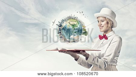 Young woman in white cylinder and red bowtie with book in hands. Elements of this image are furnished by NASA