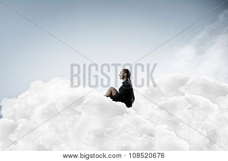 Thoughtful young businesswoman sitting alone on cloud high in sky
